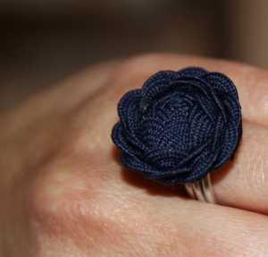 Sortija Anillo con forma de flor colocado en una mano